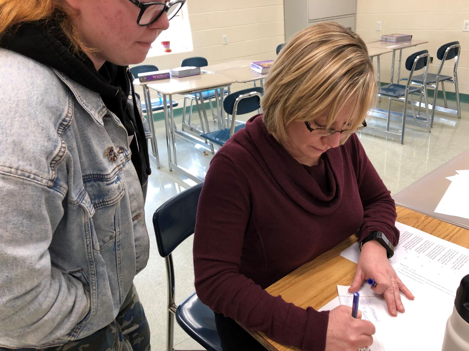 Senior Adri Portman helps educate English teacher Annette Manlief on the latest phrases used in casual conversations.   Manlief jotted down several phrases and planned to start using them when she spoke with students.