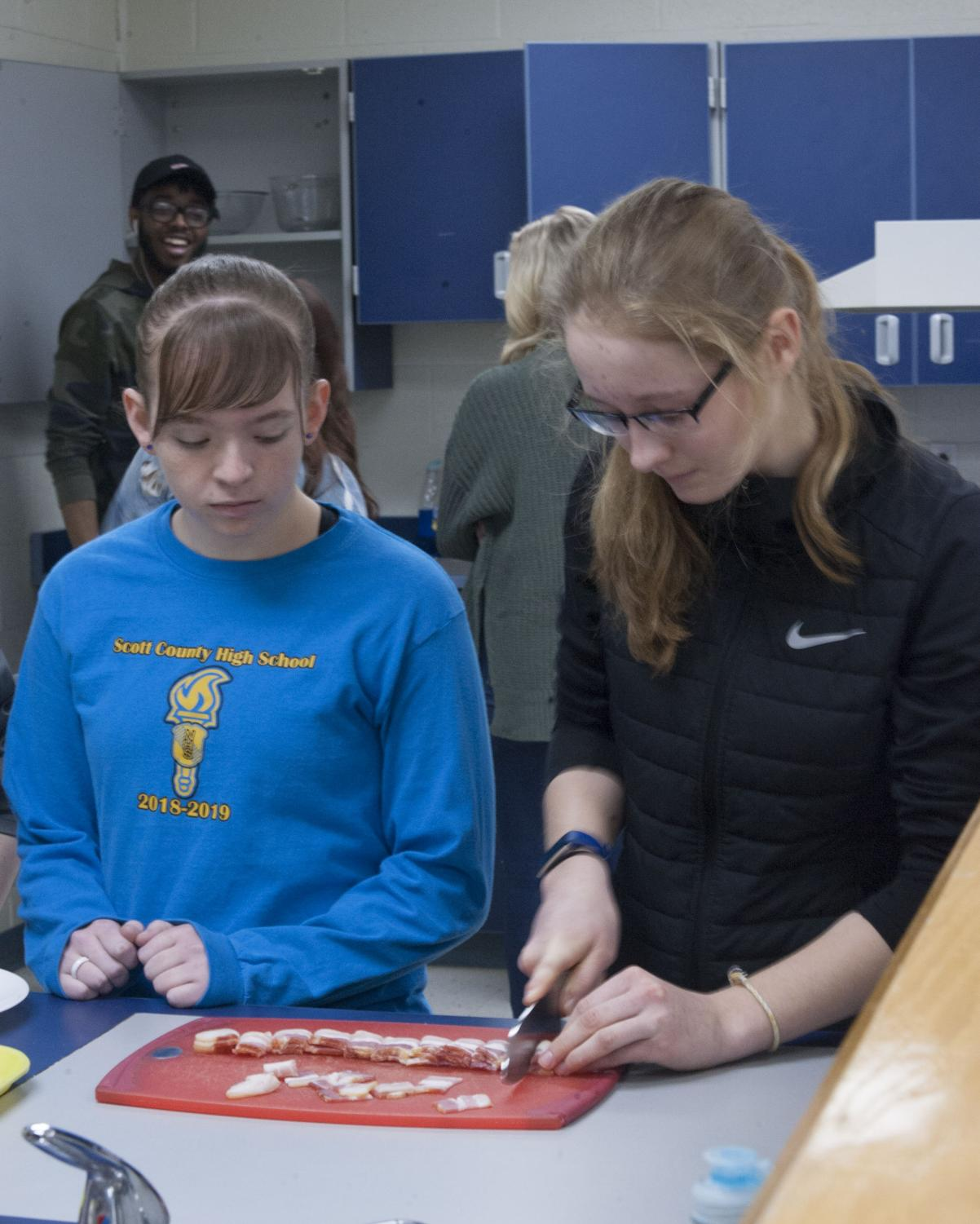 Bri Stephenson, senior, and Sophia Vetter-Ryan, sophomore, work to prepare bacon for a French quiche recipe.  Students from French and Foods and Nutrition joined forces to learn how to prepare authentic French dishes in honor of Mardi Gras.