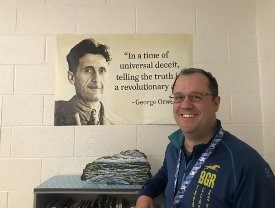 Teacher Nathan Jones smiles exuberantly next to a poster of  George Orwell