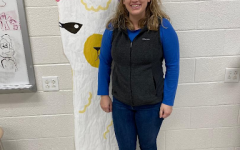 The Psychology and Arts and Humanities teacher smiles jubilantly beside a llama.